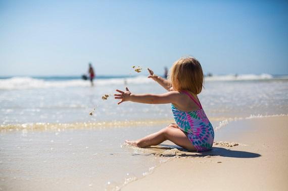 Fetita in costum pe baie, stand pe plaja