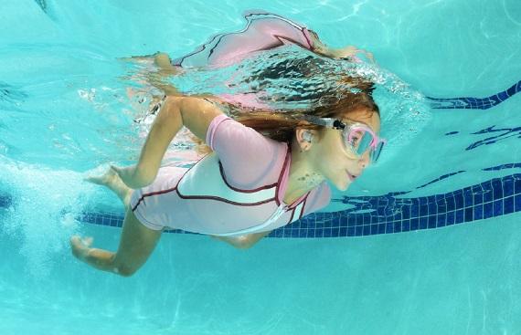Fetita care inoata, avand ochelari de inot si dopuri de inot