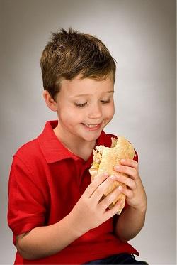 Prescolar ce mananca un sandvis