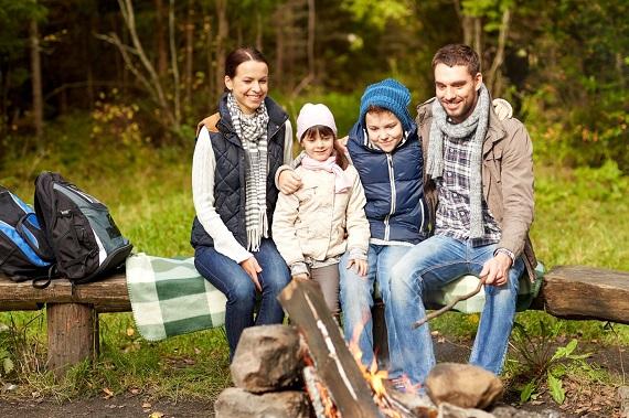Familie la iarba verde, stand langa foc