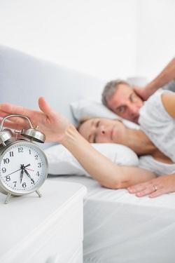 Femeie in pat, ce incearca sa opreasca ceasul ce suna