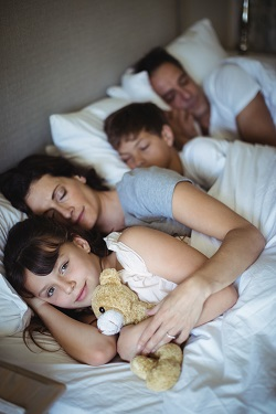 Parinti si copii dormind in acelasi pat