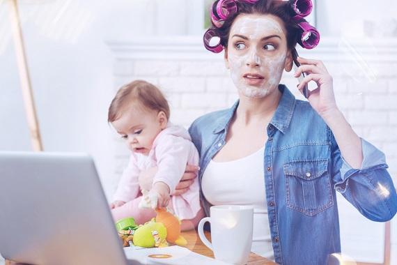 Mama cu bebelusul in brate, in timp ce incearca sa vorbeasca la telefon si sa se ocupe si de copil