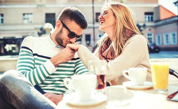 Barbat care saruta mana unei femei, in timp ce se afla la masa in oras