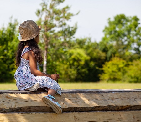 Fetita cu palarie de soare si rochita, stand pe un gard de lemn