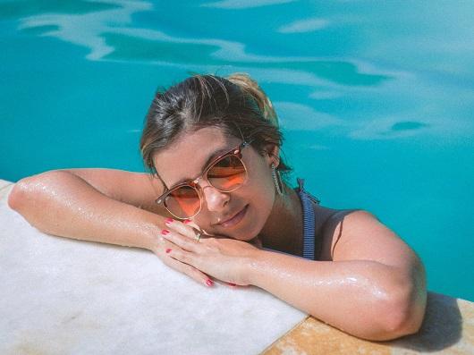Fata ce este in apa, la marginea unei piscine