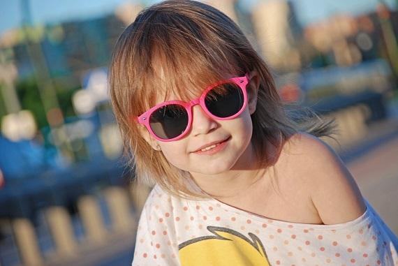 Fetita zambitoare, cu ochelari de soare roz