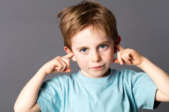 Copil care isi tine degetele din ureche