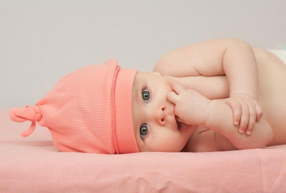 Bebelus cu o manuta in gura