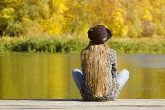 Fata cu palarie, ce sta la soare pe malul unui lac