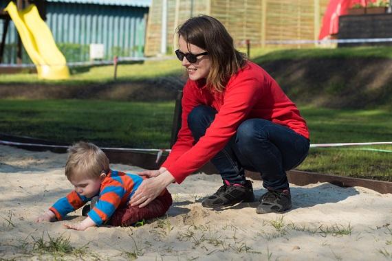 Mama ce incearca sa comunice cu bebelusul ei care se afla in groapa cu nisip si care o ignora