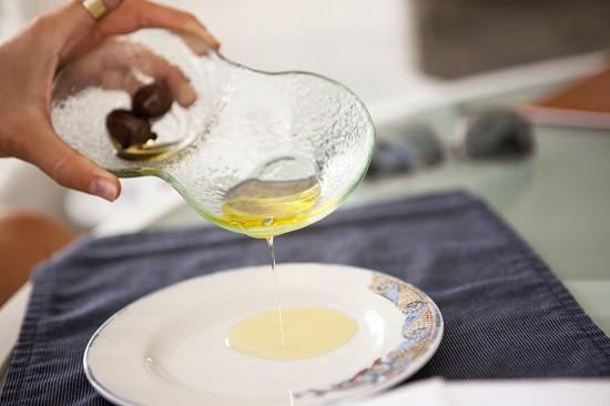 Femeie ce toarna pe farfurie ulei de masline