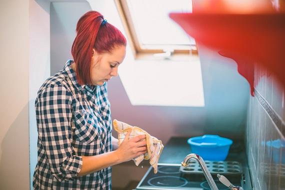 Femeie ce isi sterge vasele cu un prosop de bucatarie