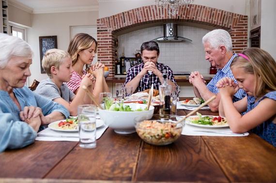 Familie la masa, spunand rugaciunea