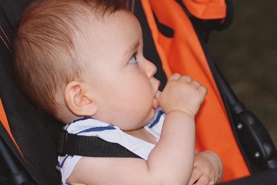 Bebelus  ce isi suge degetul si sta in scaunul auto special pentru bebelusi