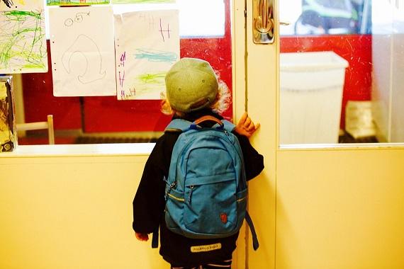 Baietel cu ghiozdanul in spate, aflat in fata usii de la o sala de clasa