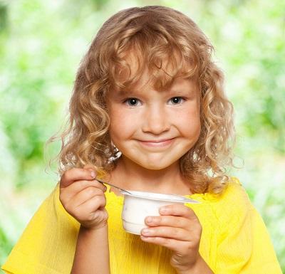 Fetita ce tine in mana un borcanel de iaurt