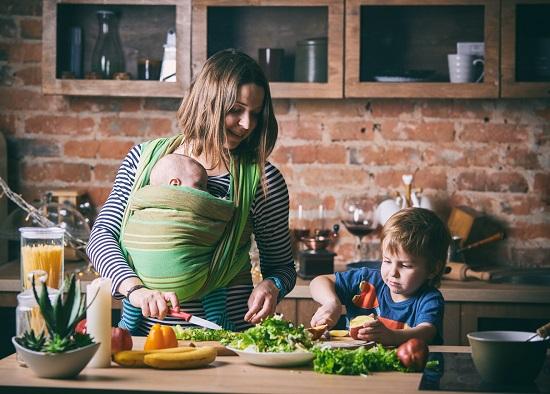 Mama cu bebelus si cu celalalt copil mai mare, gatind legume cu frunze verzi