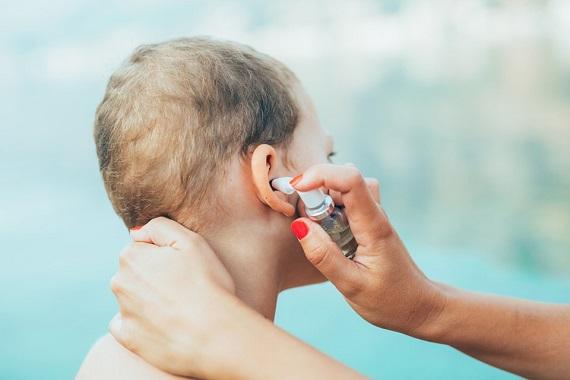 Mama care ii pune copilului ei spray de urechi