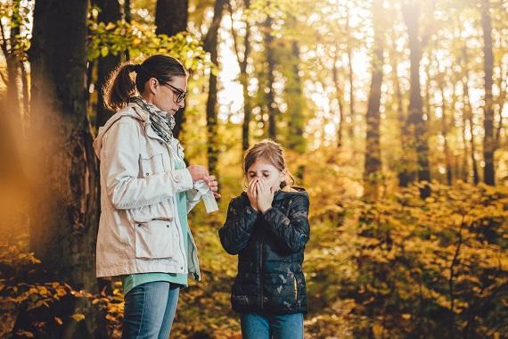Mama si fiica intr-o padure, toamna, iar fiica are probleme din cauza nasului care curge