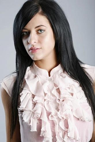 Fata ce poartao bluza roz deschis, cu volanase aplicate