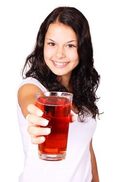 Fata ce tine in mana un pahar cu suc de rodie