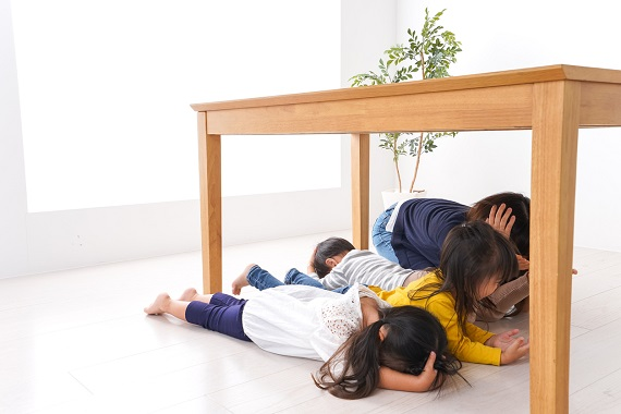 Copii ce se adapostesc sub masa, la un cutremur, alaturi de mama lor