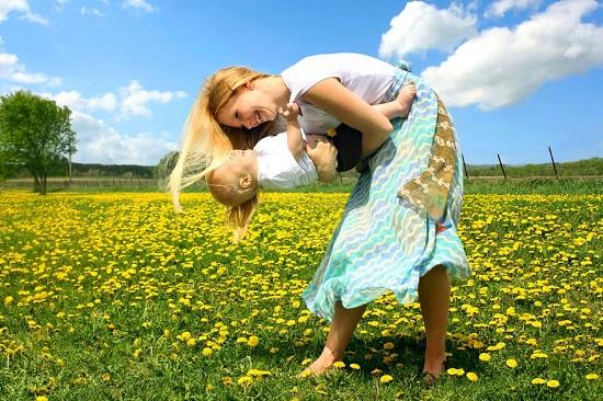Mama se joaca pe-afara cu bebelusul ei