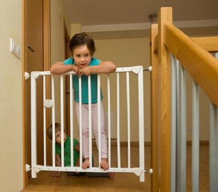 Fetita ce s-a catarat pe usita de protectie de la scarile din casa