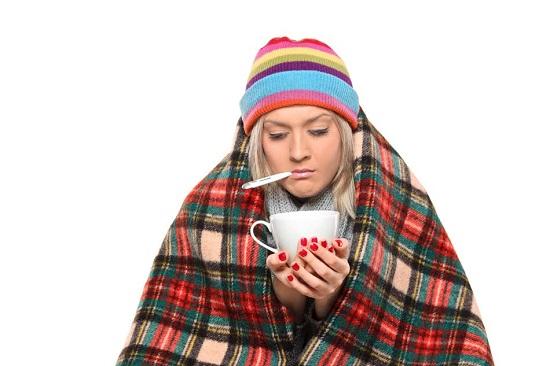 Femeie cu febra, imbracata gros si cu o cana de ceai in mana