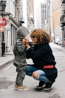 Mama ce isi tine de mana baietelul, in semn de afectiune