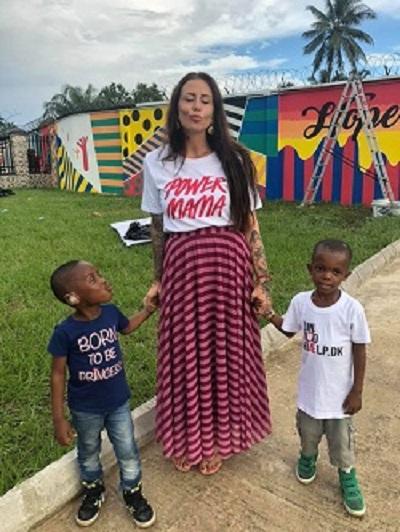 Femeie alaturi de doi copii africani