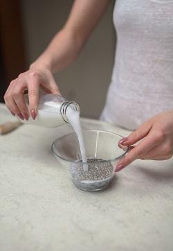 Femeie ce adauga lapte peste seminte de chia