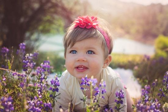 Fetita stand printre flori