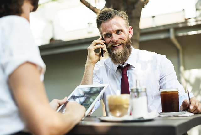 barbat care vorbeste la telefon la masa