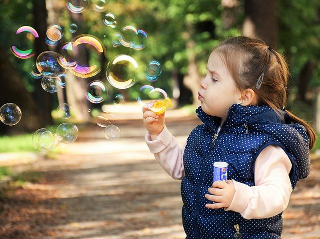 copil care se joaca cu baloane de sapun