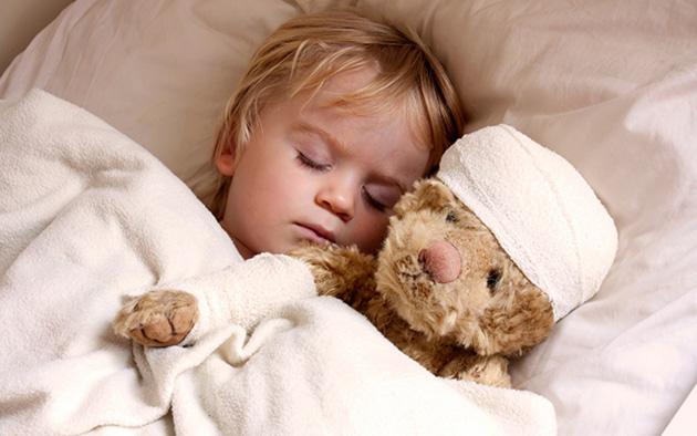 Copil doarme cu jucarie in brate