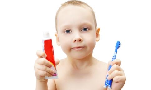 copil cu o pasta de dinti in mana