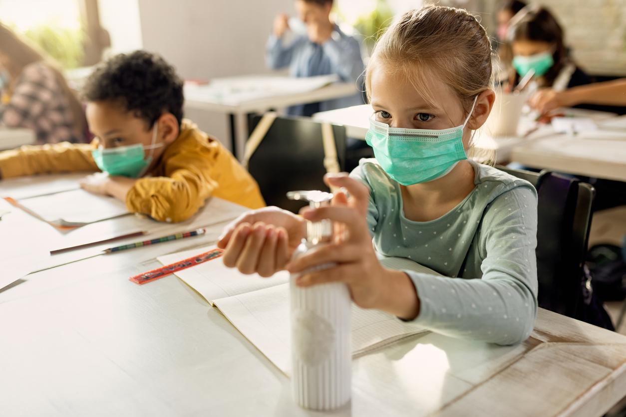 fetita in banca, la scoala, care is dezinfecteaza mainile