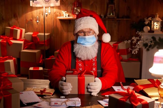 mos craciun cu masca inconjurat de cadouri