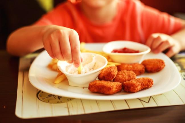 copil care mananca mancare tip fast food, cartofi prajiti si nuggets de pui