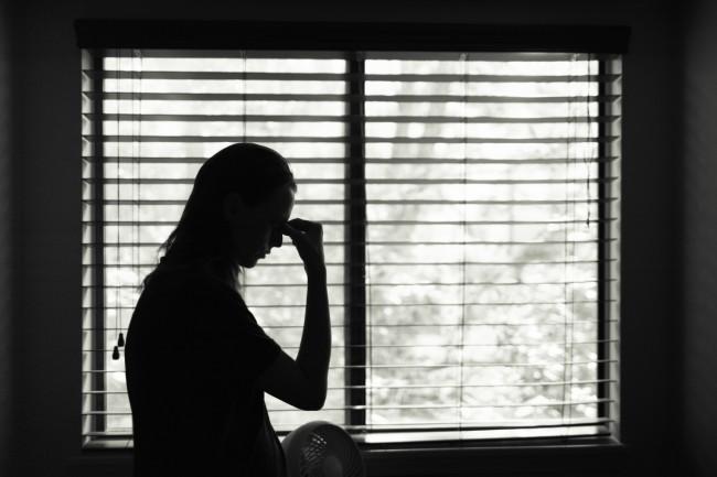 femeie obosita care sta in fata ferestrei