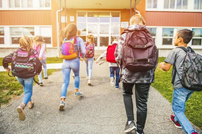 grup de copii care alearga spre scoala