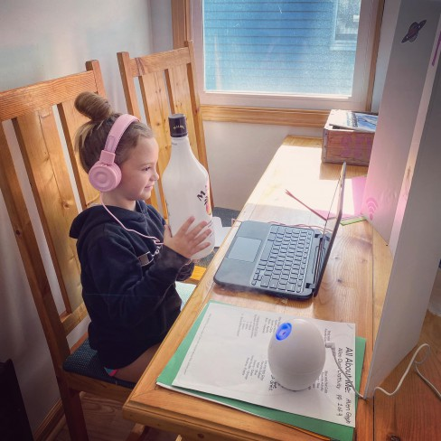 fetita care arata o sticla de rom cu cocos in timpul scolii online