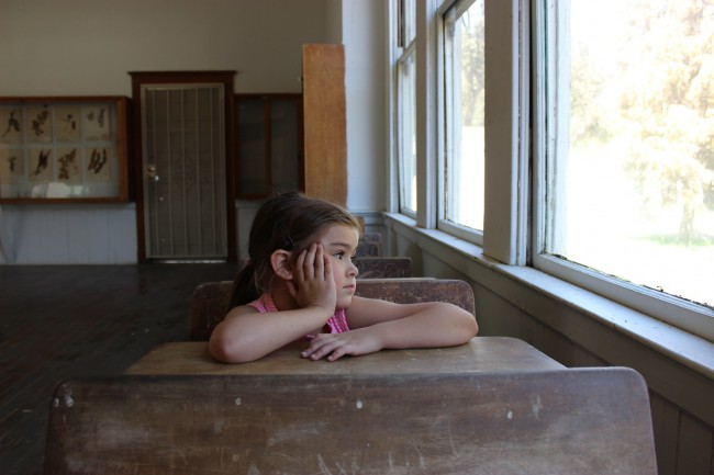 fetita care sta in banca intr-o clasa goala si priveste pe geam