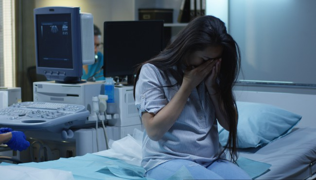 femeie care plange pe patul de spital