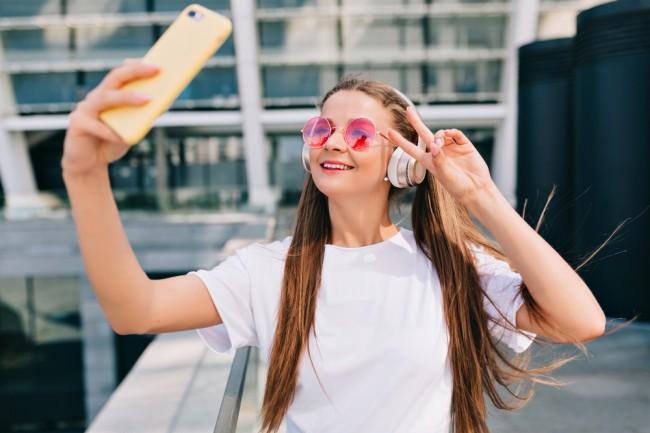 adolescenta cu ochelari de soare si casti care se filmeaza cu telefonul mobil