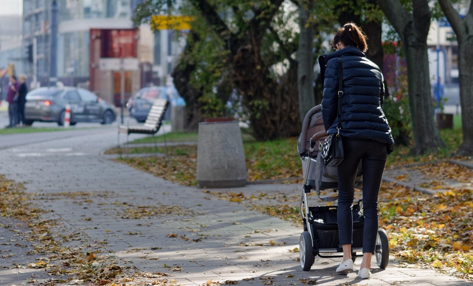 o mama care isi plimba bebelusul in carucior pe strada