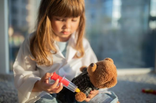 fetita care face injectie unui ursulet de plus