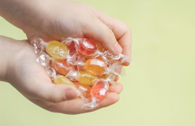copil care tine in mana mai multe bomboane ambalate